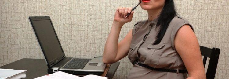 Беременная деловая женщина работает